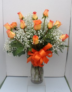 Orange long stemmed roses Arranged in glass vase