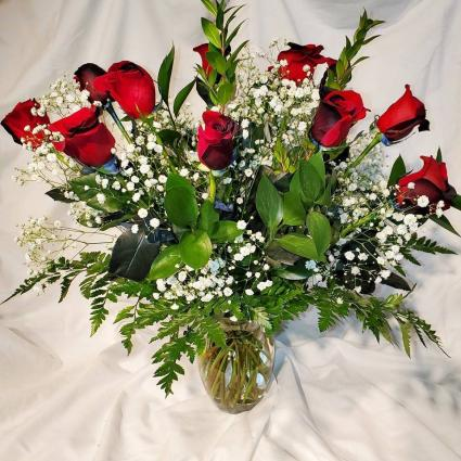 Our Love Is Magic Dozen Black Magic Roses in a Vase with Greens and Babys Breath
