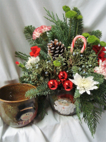 OVERSIZED COFFEE OR SOUP MUG WITH SNOWMAN OR SANTA FACE FILLED WITH RED AND WHITE FLOWERS AND CHRISTMAS GREENS!