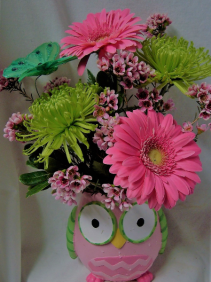"""OWL CONTAINER IN PINK OR BLUE"" FILLED WITH PINK  OR BLUE FLOWERS WITH GREEN ACCENT FLOWERS AND BUTTERFLY."