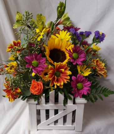 Picket wooden fence arrangement with bright Fall seasonal flowers. Nice keepsake !