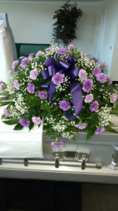 Purple carnations with baby's breath and greenery Sympathy
