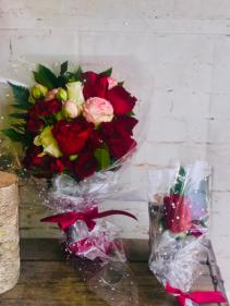 red garden rose arrangement with boutoneirre arrangement