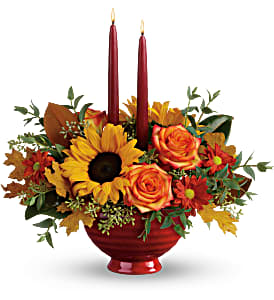 Telefloras Earthy Autumn Centerpiece Centerpiece with candles. Nice mix of lush greenery, fall daisys, orange bi color roses and sunflowers.