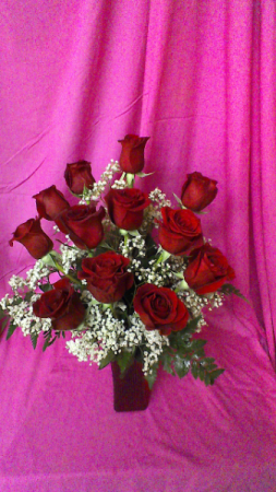R12SS Sent With Love dozen short stemmed roses and baby breath arranged in a red vase