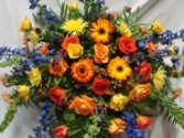 WARMEST REMEMBRANCE Half Casket Spray of seasonal shades of reds, oranges yellows and blues. Roses, gerbera daisies, delphinium, fugis and more.