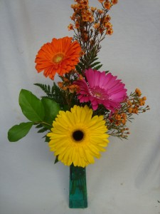 3 Bright Gerbera Daisies arranged in a tall colored vase with filler!! Very Popular!!
