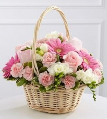 TOUCHING TRIBUTE Table arrangement to take home after services or pinks and whites in a wicker basket