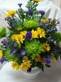 EXPRESSIONS OF SYMPATHY Flowers in shades of greens, blues, and yellows arranged