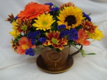 "Teacup Delight!! Tin teacup with bright fall  flowers, round so can be used as a centerpiece. Nice keepsake for a 4"" plant later(has liner)!"