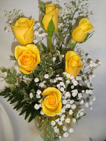 Six Bright Yellow Roses With Babys Breath Arranged In A Vase In