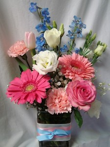 'WHITE AND BLUE COLORS WITH A WHITE ROSE FOR THE SORORITY FLOWER! ALL ARRANGED IN A CUTE RECTANGULAR VASE WITH PINK AND BLUE RIBBON DETAIL!