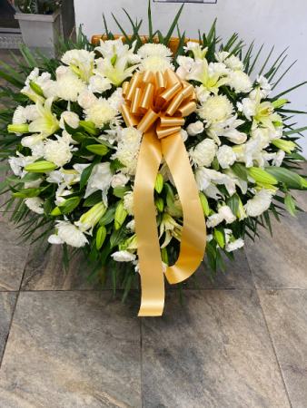 White flowers with lilies Funeral casket