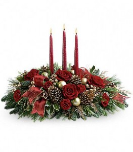 Christmas centerpiece with 3 candles with red flowers, christmas greens, balls , pine cones.
